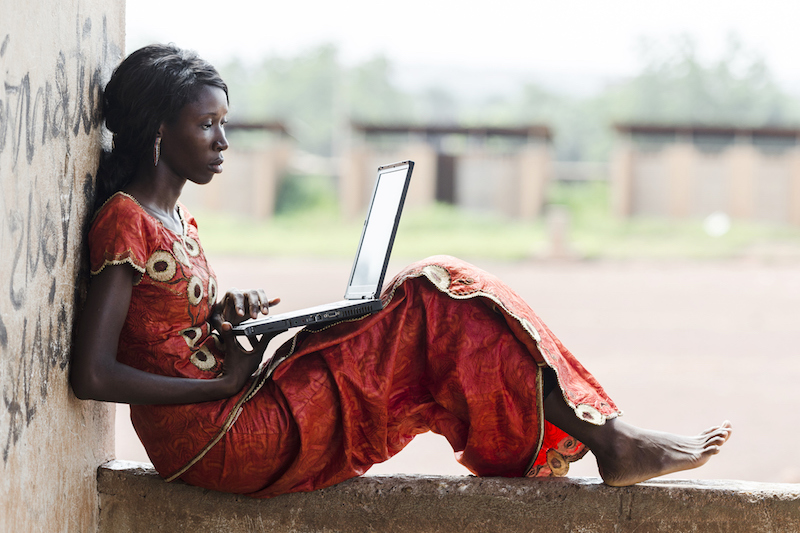 African woman in traditional colourful dress working on laptop